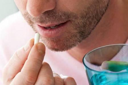 мужчина пьёт капсулу