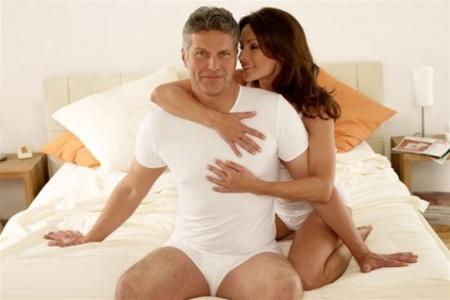 Женщина обнимает мужчину на кровати
