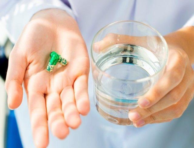 таблетки в капсулах и стакан с водой